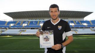 Javi Gracia, entrenador del Málaga, posa con el Manual de Bienvenida en La Rosaleda