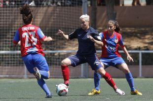 Priscila, del At. Madrid Féminas, intenta deshacerse de dos rivales del Levante Femenino.